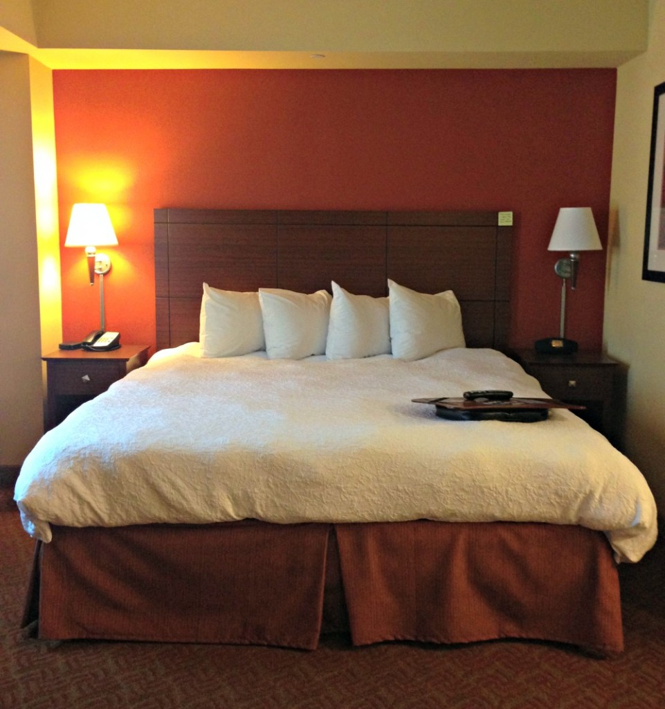A cosy king sized bed at Hampton Inn & Suites